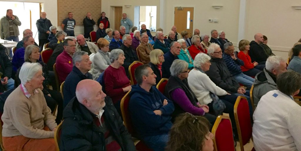 View of packed village hall with people standing at rear